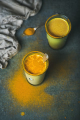 Golden milk with turmeric powder in glasses over dark grunge background, copy space. Health or energy boosting, flu remedy, natural cold fighting drink. Clean eating, dieting, weight loss concept