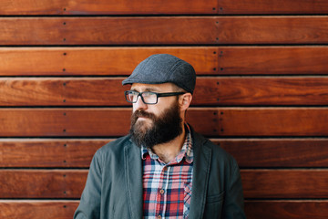 Trendy male looking away on wooden wall