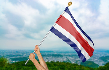 Young man's hands proudly waving the Costa Rica national flag in the sky, part 3D rendering