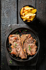 Tasty tbone steak and chips with herbs and salt