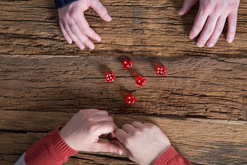 Two men playing dices on old wooden table. Top view.