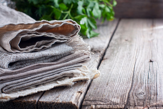 Clean beige kitchen linen towels on a wooden table, Horizontal, copy space