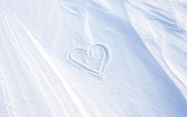 Heart in winter season write on the snow