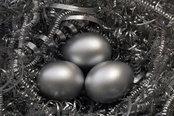 Three silver eggs in a nest of metal shavings