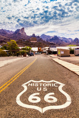 Historic US Route 66 with highway sign on asphalt and a panoramic view of Oatman, Arizona, United States. The picture was made during a motorcycle road trip through the south western states of USA.