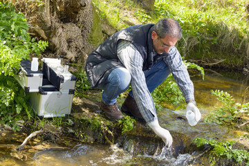View of a Biologist take a sample in a river.
