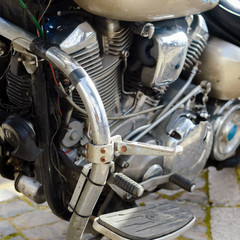 Close up on shiny chrome motorcycle details, silver background