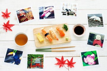 Traveling to Japan / memories of Japan concept.  Japan view travel photo, sushi set, green tea, red maple leaves on a white table.