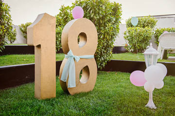 Number eighteen gold color over green grass. Party decoration
