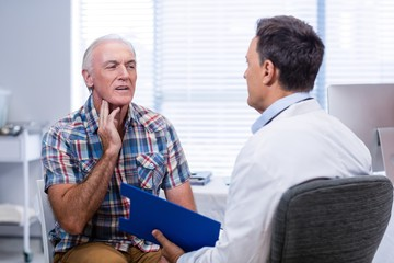 Senior man showing neck pain to doctor
