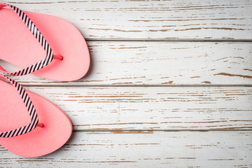 Pink flip flops on white wooden background