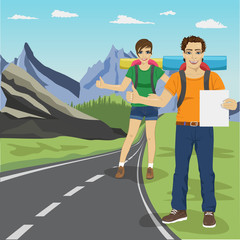 Young man and woman hitchhiking on road in mountains