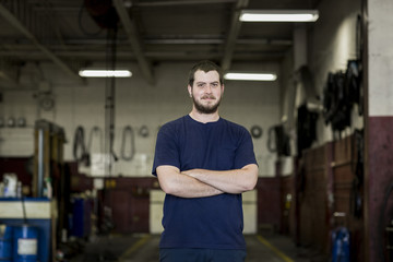 Portrait of blue collar worker in warehouse with arms crossed