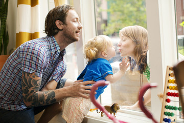 Father and little girl (18-23 months) blowing a kiss through window to mother