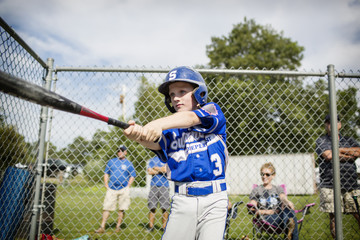 Young baseball player training on field