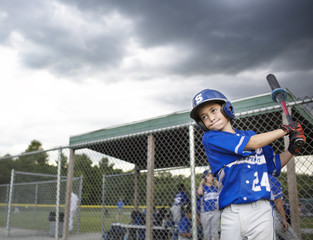 Little league player (10-11) practicing swing with bat