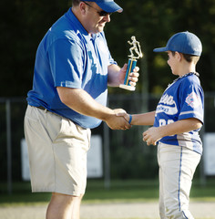 Coach presenting trophy to little league player (8-9)