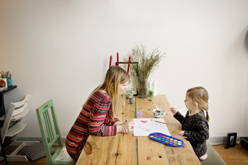 Mother and daughter (4-5) painting picture