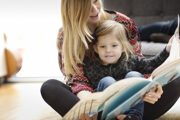 Mother and daughter (4-5) reading picture book