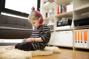 Girl (4-5) sitting on rug listening to music