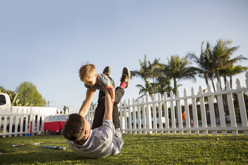 Father playing with son (2-3) outdoors