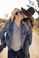 Young couple riding piggyback and kissing