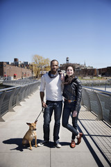 Portrait of couple with dog on bridge