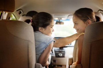 Mother and daughter (8-9) looking at each other in car