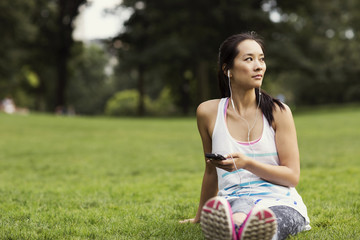 Woman with smartphone sitting in park
