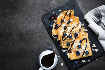 Crepes with blueberries almond flakes and chocolate sauce on black. Top view