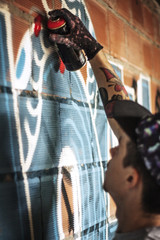 Young man using spray to create graffiti