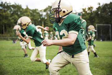 Boys playing American football on field