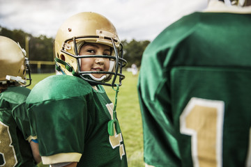 Boy (6-7) playing american football