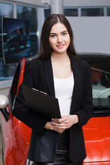 Beautiful female seller shows the car