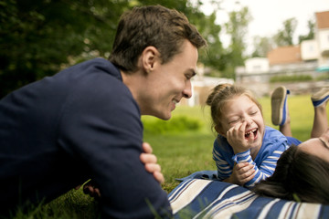 Father laughing with daughter (6-7) in backyard