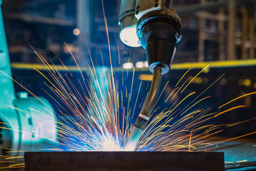 Close-up industrial robot is welding in a car factory