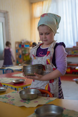 A little girl dressed in an apron puts the dishes on the table in the kindergarten