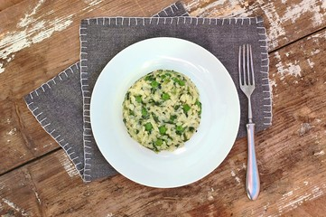 Creamy risotto with peas and spinach on white plate on grey cloth on rustic table