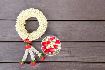 Garland Flowers made from Jasmine, Rose Petals and Crown flowers with a small silver bowl contain water and flower corolla on top isolated on wooden background (Use for Songkran Holiday in Thailand)