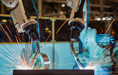 Close-up robots are welding in a car factory