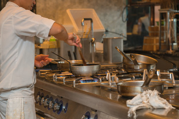 chef cooking with pan in the kitchen