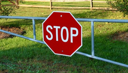 A stop sign on a metal gate.