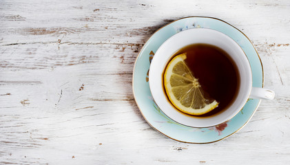 Cup of green tea with lemon on rustic wooden table