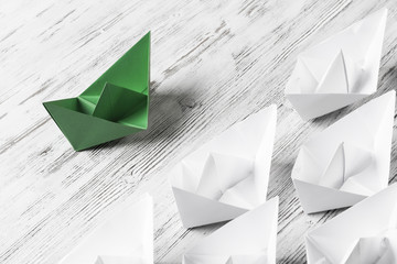 Business leadership concept with white and color paper boats on