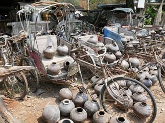 Old tricycles lined up on the ground with old jars, traditional samlor in thailand, vintage background