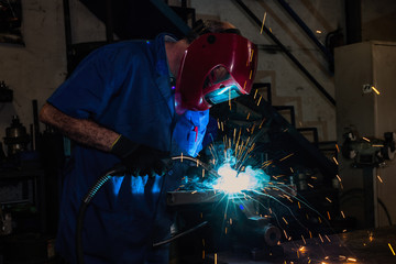 Welder wearing face mask and protective gloves in factory