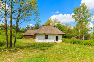 Old traditional houses with straw roofs in Tokarnia village on sunny spring day, Poland