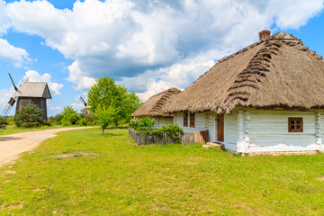 Old traditional houses with straw roof in Tokarnia village on sunny spring day, Poland