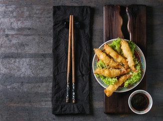 Fried tempura shrimps on lettuce salad with sauce. Served in traditional china plate with chopsticks on wood serving board and textile napkin over old metal background. Top view, space. Asian dinner