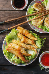 Fried tempura shrimps and gyozas potstickers on lettuce salad with sauces and rice. Served in traditional china plate with chopsticks over old wooden background. Top view. Asian dinner